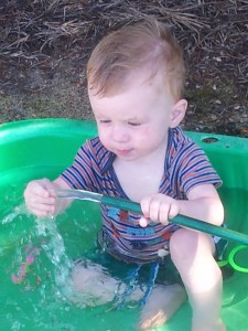 Josiah playing in paddling pool